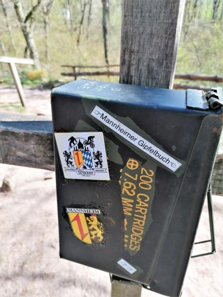 In einem Metallkasten findet sich das Gipfelbuch der höchsten natürlichen Erhebung Mannheims, gelegen im Dossenwald.